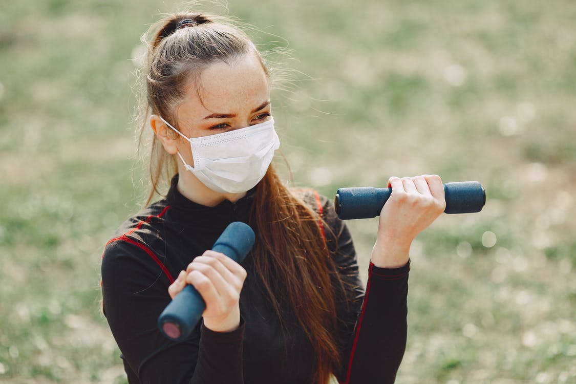 Slender young lady in face mask and sports clothes looking away while exercising with dumbbells outdoors in daylight during quarantine time