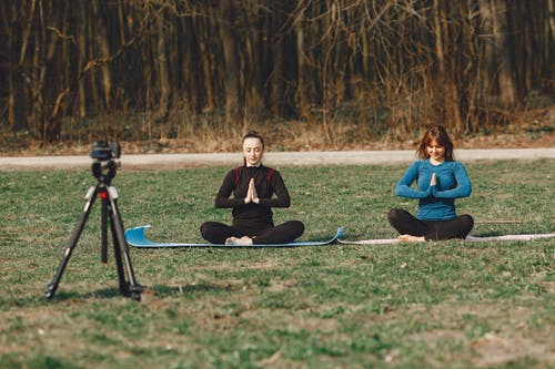 Calm young female friends in sportswear sitting with crossed legs and closed eyes in Namaste pose in front of tripod with photo camera on grass