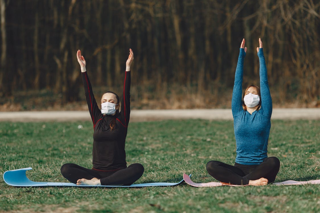 Girlfriends sitting in lotus pose with raised hands outdoors