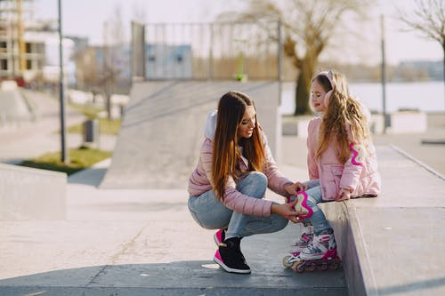 Mother and daughter in warm outerwear on skate playground before roller skating