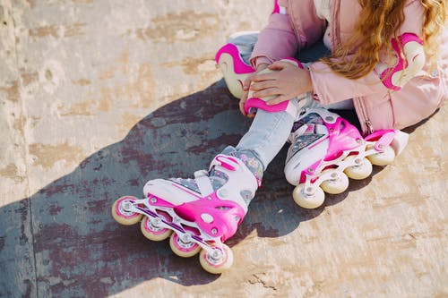 From above of anonymous little girl wearing warm pink jacket sitting on concrete ground in roller skates during active leisure