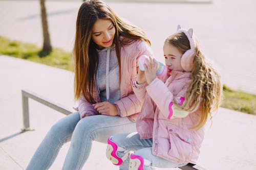 Cheerful young mother in warm pink jacket sitting near little girl in fur earmuffs and protection pads for skating or riding while drinking water from plastic bottle