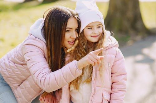 Woman in Pink Jacket Hugging Girl in White Hoodie