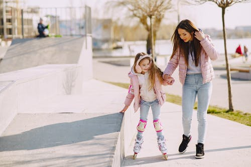 Cheerful girl skating on rollers with young mother