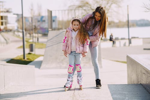 Full body cheerful young woman supporting daughter wearing protection pads while roller skating on concrete ramp during active leisure in sunny spring day