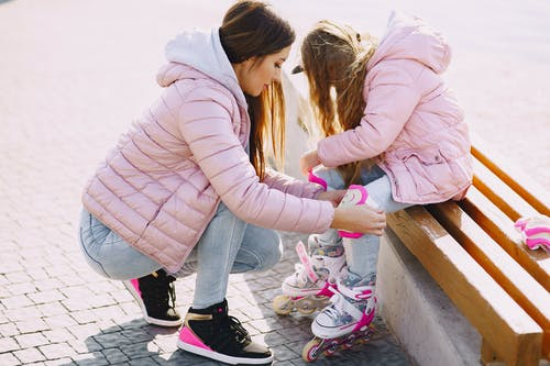 Woman in Pink Jacket and Blue Denim Jeans Holding Girl in Pink Jacket