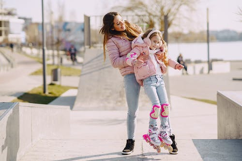Woman in Pink Jacket and Blue Denim Jeans Carrying Girl in Pink Jacket