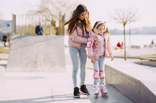 Full body focused young woman supporting daughter wearing protection pads while roller skating on concrete ramp during active leisure in sunny spring day