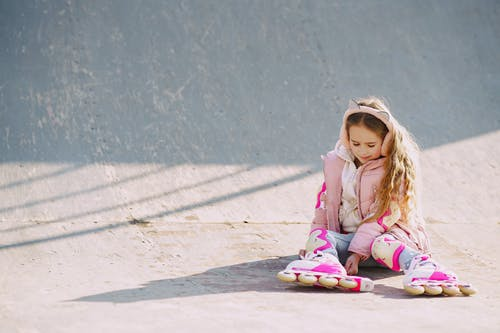 Girl in Pink Jacket and Pink Pants Sitting on Concrete Floor