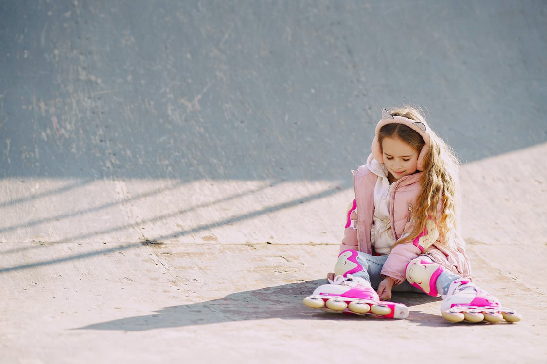 Smiling cute child in roller skates sitting on skate ramp