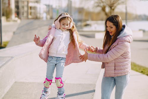 Smiling little girl practicing skating on roller skates with mother