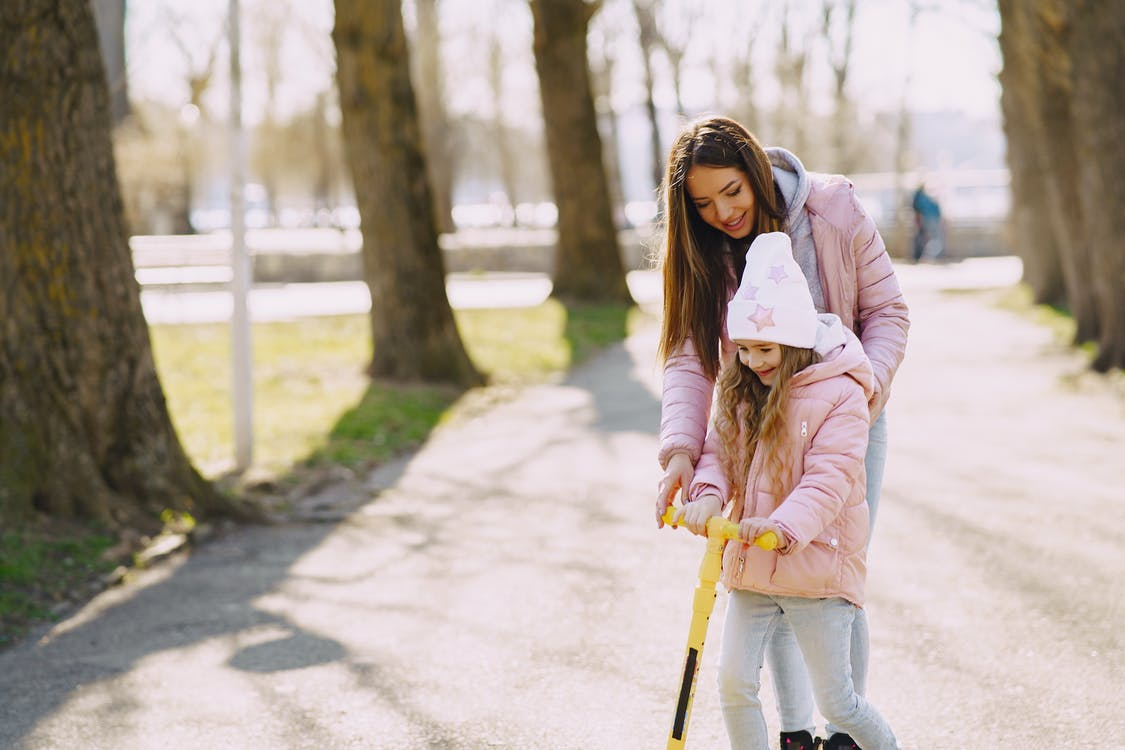 Woman and girl spending time in park with kick scooter
