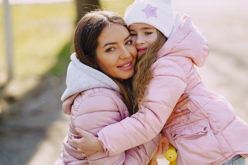 Girl in Pink Jacket Hugging Girl in Pink Jacket
