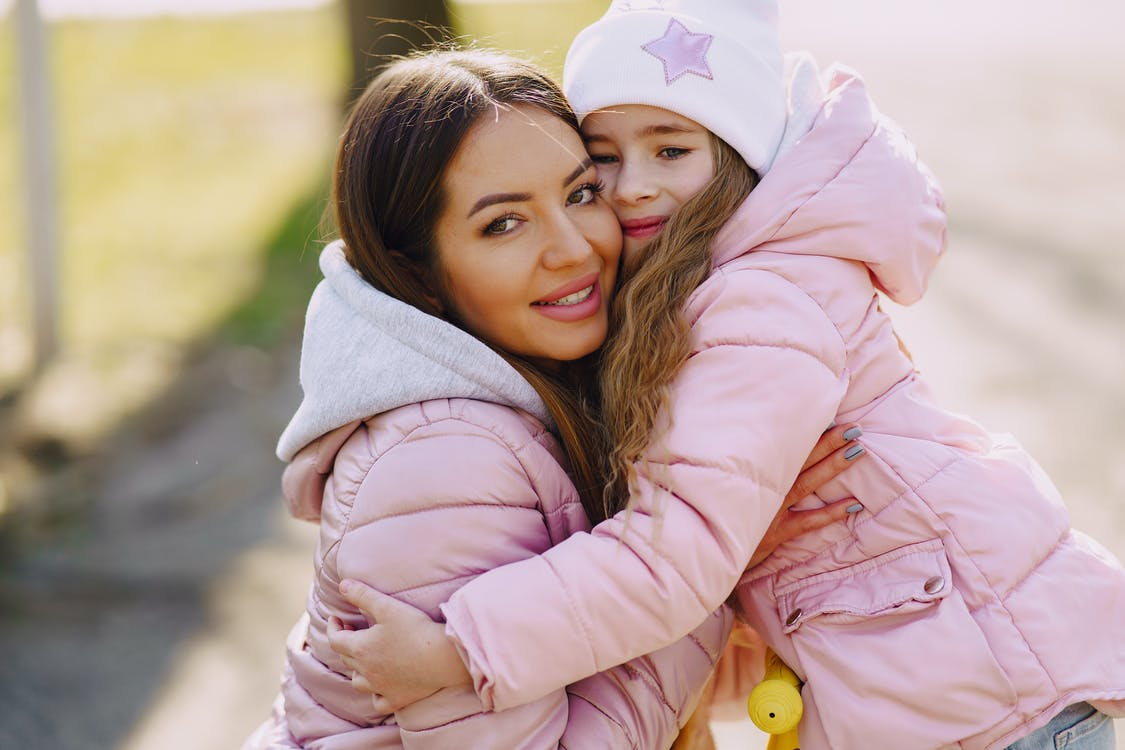 Happy mother and daughter embracing in spring in park