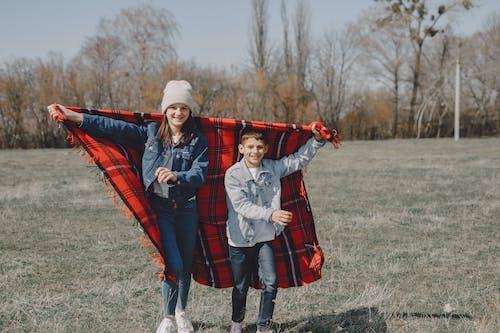 Cheerful kids running with blanket in lawn in autumn season