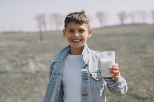 Boy in Blue Denim Jacket Holding White Cup