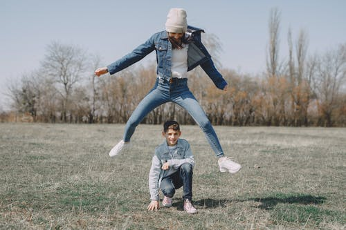 Woman in Blue Jacket and Blue Denim Jeans Jumping on Green Grass Field