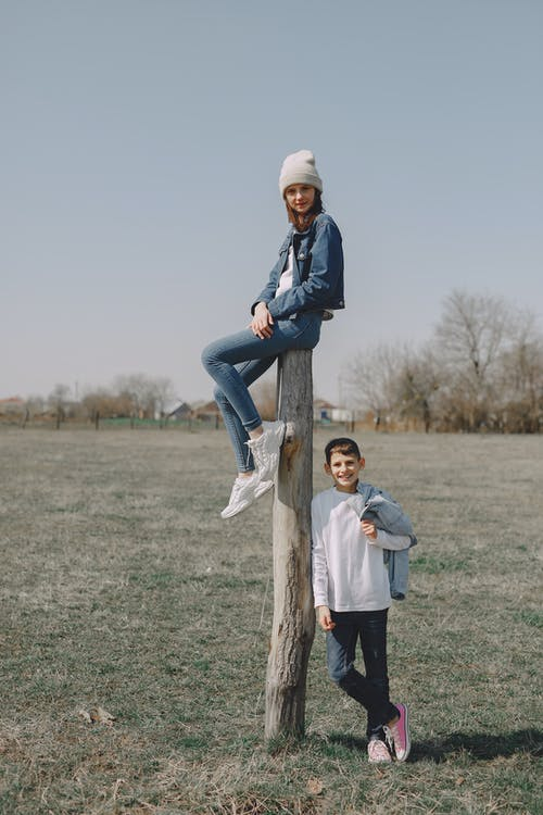 Girl sitting on pillar and boy standing near in countryside