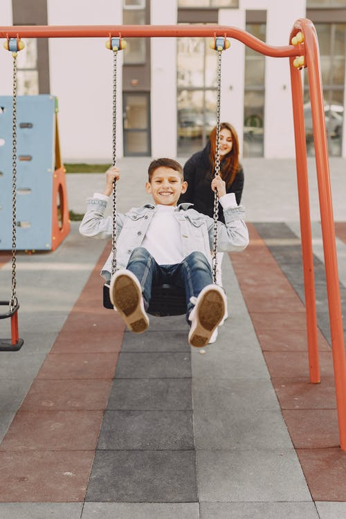 Joyful boy swinging on swing on playground