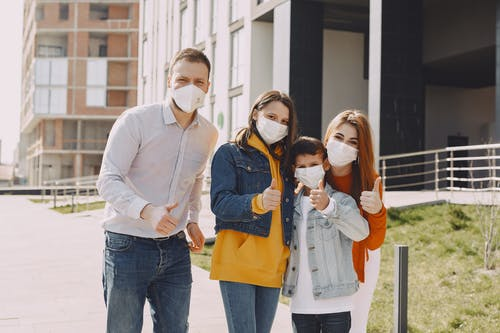 Happy family in medical masks on city street