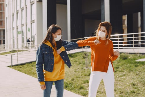 Young women in medical masks greeting each other on city street