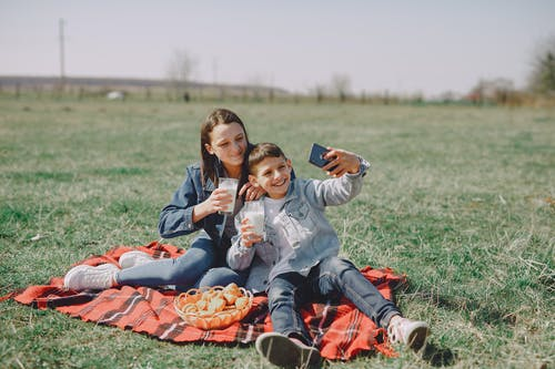 Cheerful friends taking selfie on smartphone in countryside