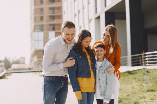 Smiling family standing together on street