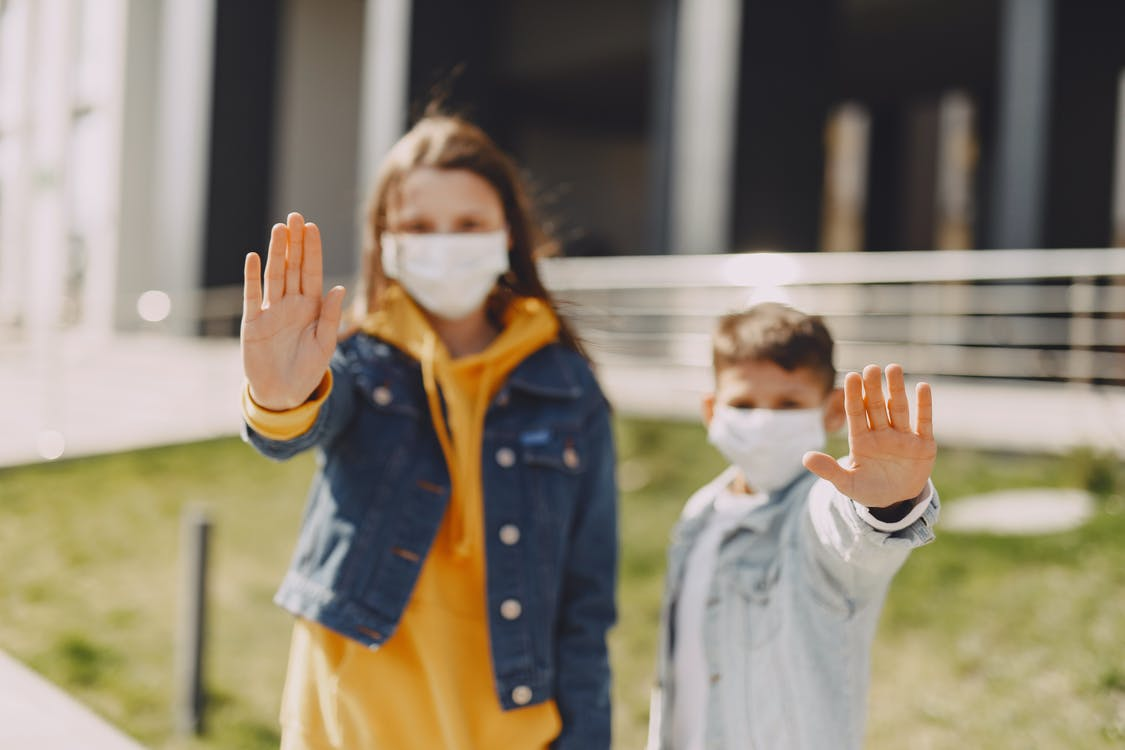 Young friends with medical masks on street