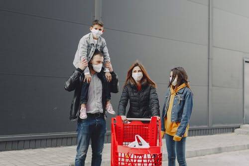 Family in protective masks with trolley on street