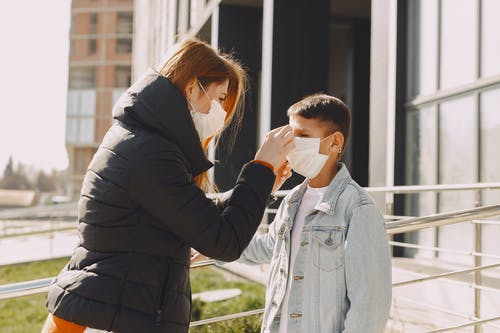 Woman fixing protective mask on kid face