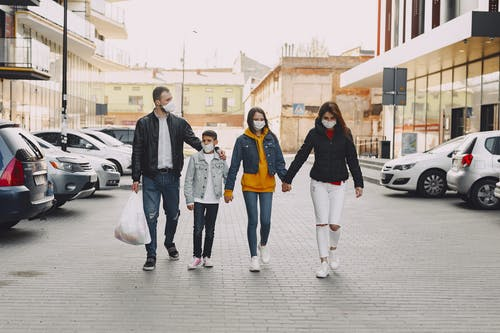Young family in medical masks walking along parking