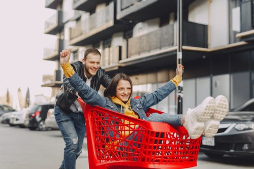 Woman in Blue Denim Jacket Holding Red Plastic Basket With Woman in Blue Denim Jacket