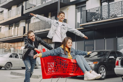 Woman in Blue Denim Jacket Holding Red Shopping Cart With Woman in Gray Jacket