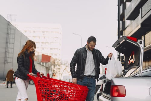 Man in Gray Jacket Holding Red Shopping Cart