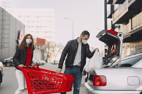 Couple in protective masks moving shopping bags to trunk