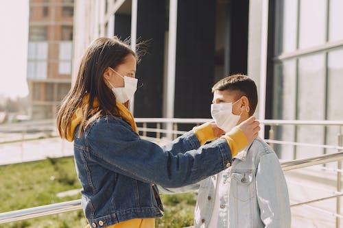 Girl in medical mask fixing medical mask on boy face