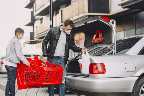 Man and boy in protective masks putting shopping bag in trunk