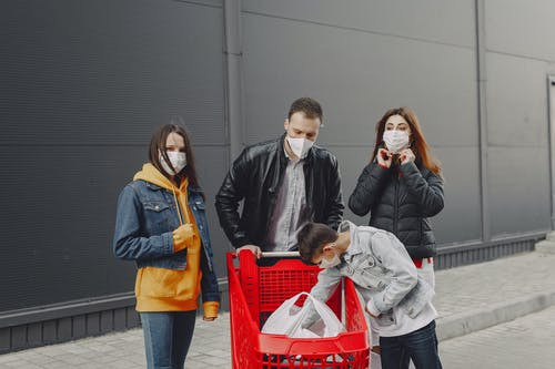 Young family in protective masks with shopping trolley on street