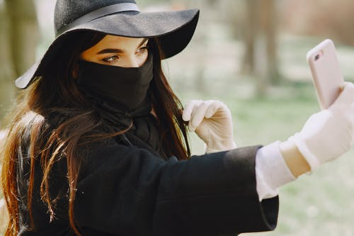 Woman in Black Hat and Black Long Sleeve Shirt