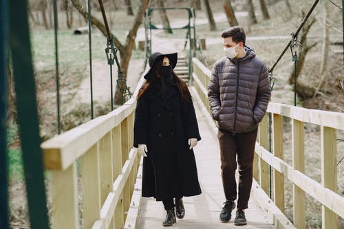 Couple walking along bridge in park