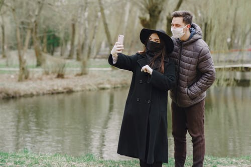 Couple taking selfie in protective masks in park
