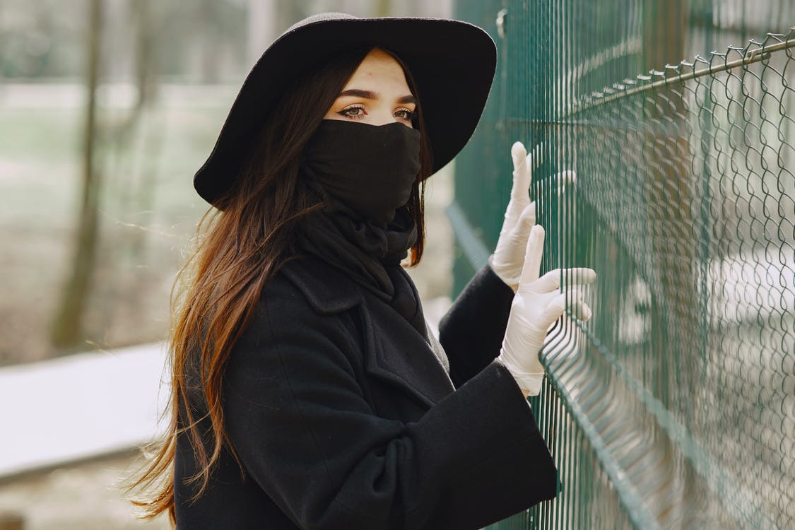 Unrecognizable lady in medical protection holding and looking through fence