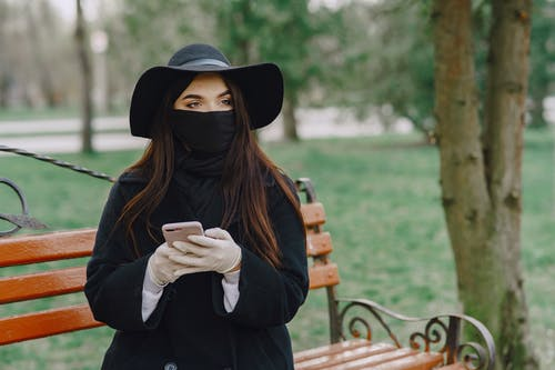 Woman in protective mask and gloves using smartphone in park