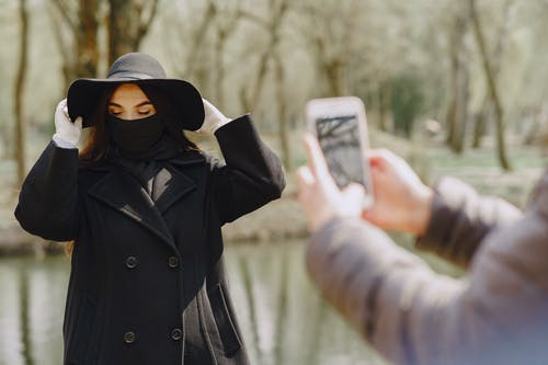 Woman in Black Coat Holding White Smartphone