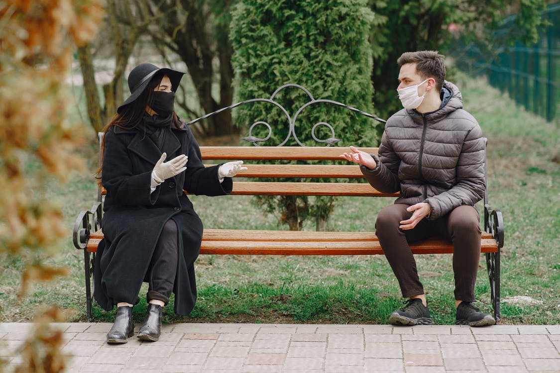 Young couple in protective gloves and masks chatting on bench in park