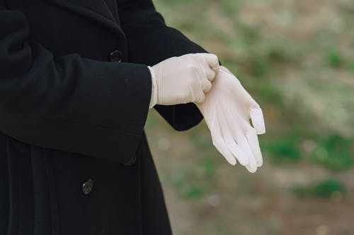 Person in Black Coat Holding Hands With White Ring