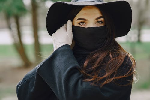 Woman in protective gloves and mask in park