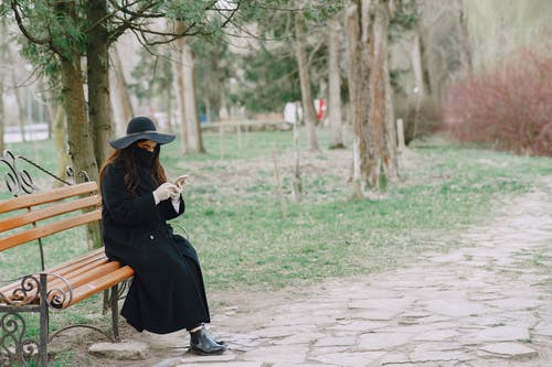 Woman in mask and gloves browsing smartphone in park