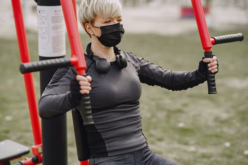 Determined sportswoman in mask working out on street sport equipment