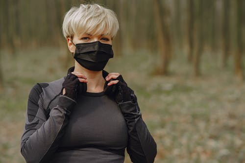 Woman in sportswear and protective mask in park
